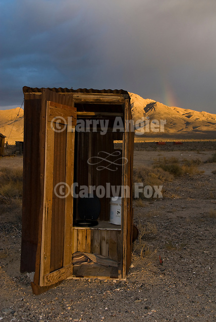 Outhouse with rainbow; clearing storm at a ghost town in Nevada.