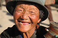 A toothless Tibetan pilgram smiles brightly for the camera in front of the Jokhang Temple. Many Tibetans travel days, months, and even years, on pilgrimage to Tibet's most sacred Temple..