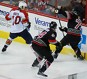 Carolina defenseman Joe Corvo peels the puck off of the boards as Panther David Booth tries to keep the puck in the Canes' defensive zone.