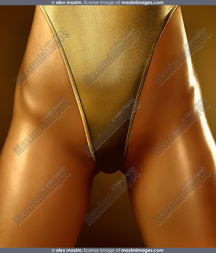 Closeup of a sexy young woman with gold body wearing a golden high-cut double dip swimsuit