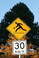 Children playing and speed limit road signs, Vancouver, BC, Canada