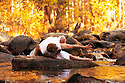 Man in yoga posture outdoors in a forest river.