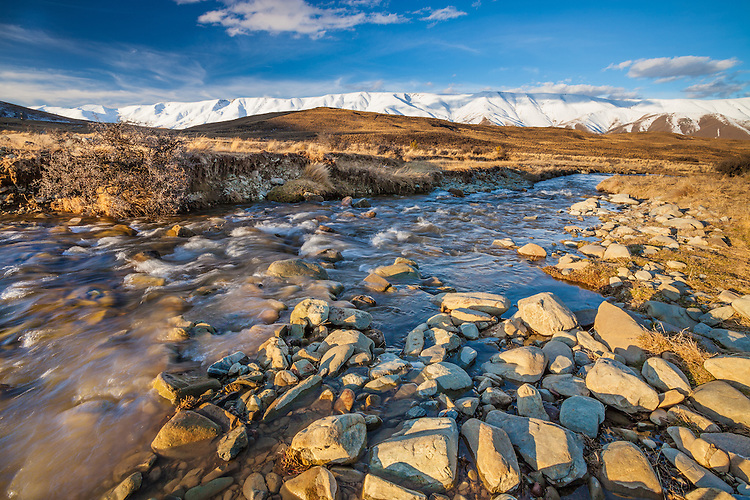 Low angle shot of a stream through tussock country with the snow covered Hawkduns behind, Central Otago, New Zealand