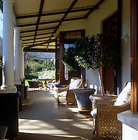 A row of white columns supports the corrugated iron roof of this sunny veranda which is furnished with wicker chairs