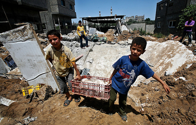 Palestinian boys inspect the damage at a cheese factory in Gaza City on June 4, 2012 following an Israeli air strike on the Gaza Strip on June 3. Emergency medical sources in Gaza said seven Palestinians were wounded in four strikes, two on targets east of Khan Yunis in the southern part of the territory, and two that hit Beit Lahiya in the northern section of the Strip. Photo by Ali Jadallah
