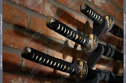 Samurai sword set Japanese Katana Wakizashi and Tanto blades in scabbards on a Bushido display stand over grungy brick wall background