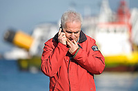 Island of Giglio, Italy, January 15, 2012. Il Sindaco dell'Isola del Giglio, Sergio Ortelli parla al telefono nel porto del Giglio..The Mayor of Island of Giglio, Sergio Ortelli, speaks on the mobile telephone at the port of Island of Giglio. Behind is seen the Concordia cruise ship.