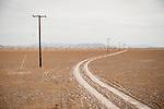 Dirt road, piles, power lines on the lake playa of Bristol Lake, Calif.