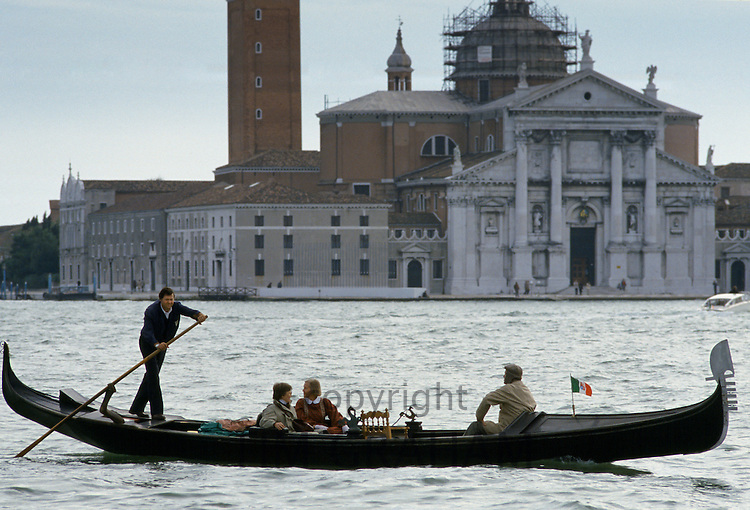 Tourists taking gondola ride propelled by gondolier along canal in Venice, Italy