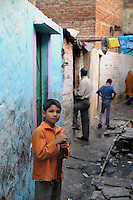 A boy in an alley of Katputly colony in New Delhi, India. 17.11.2009. Kathputly colony is a slum area in West Delhi. This slum seems like any other slum areas of modern India with dysfunctional electricity, non existing sanitation and poverty. As a part of Delhi, this is also ailed with water crisis. Large families live their lives crammed together in a single room with all the odds which complement poverty. One thing which differentiates this slum with any other is the people living in the colony. Nearly everybody in this slum is a traditional performing artist; and they have been migrating to this area for last 50 years from different parts of the country for a better livelihood. They are magicians, acrobats, jugglers, puppeteers, dancers and musicians. These artistes perform in star rated hotels, marriage ceremonies of the richer section, functions, and festivities all around the country and the world. Most of the artisans I met here, have performed in Europe and America but such opportunities are rare to come by. They struggle to keep their art form alive. They say that they don't get any help or support from the government for their basic needs and for the well being of the Kathputly colony -  though they have uphold the prestige of the country internationally. Polluted air, dirty alleys smelling of urine, colourful dress and sound of music characterise Kathputly colony, which is the one of its kind in India. Arindam Mukherjee