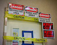 Safety reminders, no trespassing and danger signs bar entry during an asbestos remediation project in New York on Friday, September 27, 2013. (© Richard B. Levine)