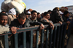 Men wait behind a barricade to board a bus at the Tunisia-Libya border near Ben Guerdane, Tunisia, Friday, Feb. 26, 2011. Thousands of foreign workers continued their exodus across the border into Tunisia, fleeing violence sparked by an uprising against Col Muammar Qaddafi. The refugees, primarily Egyptians, had to wait at the border or at an improvised camp nearby until a bus could take them to the airport in Tunis.