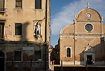A woman looks out from the shadows of a narrow street at the Santa Maria dei Carmini church on the Rio de San Margherita canal in Dorsoduro, a district of Venice, Italy.
