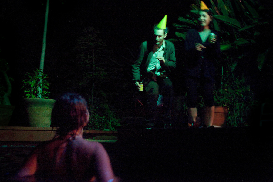 Los Angeles, California, August 1, 2009 - Warpaint guitarist/singer, Emily Kokal enjoys the pool while drummer, Josh Klinghoffer  and bassist, Jenny Lee Lindberg dance with party hats at the home of Moonrats guitarist, Nathan Thelen in the hills above Studio City. The two bands just finished a 10-day tour of the west coast and ended the tour with a relaxing night of swimming. ..