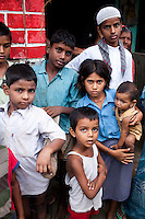 "Sitara's (aged 35, unseen) children Ajman (5, centre bottom), Roshni (10, girl in blue), and Tamanna (8 months, baby) stand with their neighbours outside their house in a village in Allahabad, Uttar Pradesh, India. ""I wish that I could stop getting pregnant but our religion says that children are a gift of God."" says Sitara, an illiterate muslim lady whose husband works as a vegetable vendor in the local village market. They have resisted all advises of permanent sterilization from the local village-level health workers. In India, male children are preferred and wives are often pressured heavily into trying for more male children immediately after finding out that their newborns are female. Sex determination ultrasounds are illegal in India due to high female foeticide cases. Allahabad, a poorer district of the state of Uttar Pradesh, is the most populated district of the most populous state of India. While Ghaziabad, located close to India's capital city, Delhi, has a population of 4,661,452 with a sex ratio of 878 girls against every 1000 boys, and a high literary percentage of 85%, Allahabad, has a population of 5,959,798 and a sex ratio of 902 girls against every 1000 boys and a literacy rate of 74.41%. Photo by Suzanne Lee / Panos London"