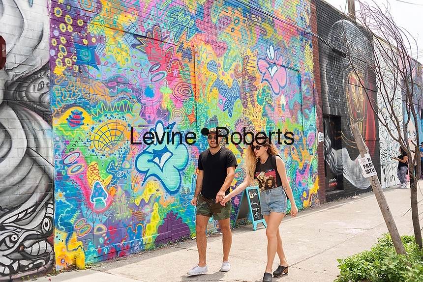 """Visitors in front of Plasmaburg's mural in Bushwick, Brooklyn in New York during the annual Bushwick Collective Block Party on Saturday, June 4, 2016. Music and partying brought some but the real attraction was the new murals  by """"graffiti"""" artists that decorate the walls of the buildings that the collective uses.  (©Richard B. Levine)"""