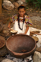 Maya girl roasting cacao beans at the recreation of an ancient Mayan market, Sacred Mayan Journey 2011 event, Riviera Maya, Quintana Roo, Mexico