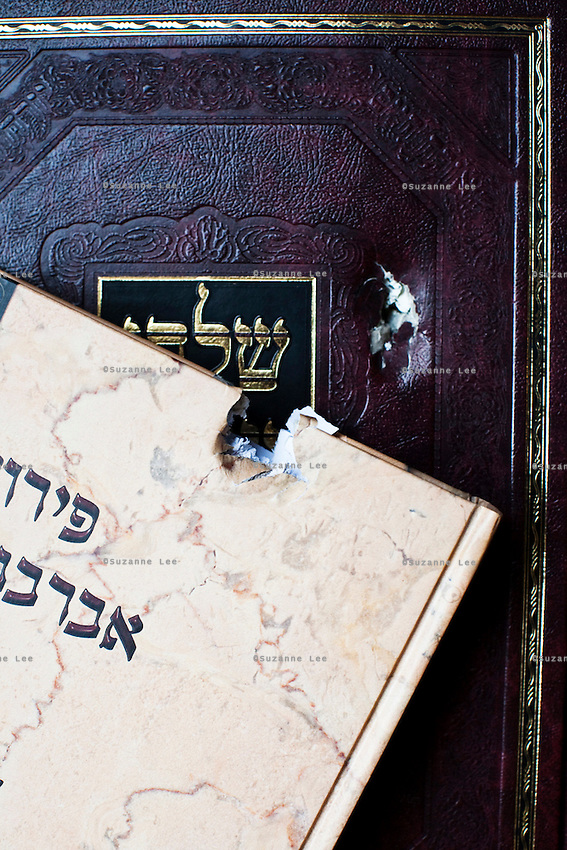Bullet holes in religious books that were salvaged from the Nariman Chabad house that was attacked in the 26/11 terrorist attacks in Mumbai, India. Mumbai Chabad was known to have an extensive library of Jewish books.