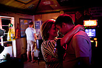 """Clean up workers from left, Kresha Trahan, 32 of Lake Charles, LA, and a man who wished to remain unidentified, share a dance at Arties Sports Bar  in Grand Isle, LA on June 23, 2010 where oil has reached land. """"Its bittersweet - I love being here. I didn't have a job back home, and now I am able to support my two kids."""""""