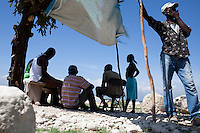 People sit in the shade at the Corail camp on July 6, 2010 in Port-au-Prince, Haiti. The camp, located far on the outskirts of the city, houses mostly people who chose to leave the crowded camp located on a former golf course in Petionville.