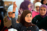 A girl raises her hand in class in the Zaatari Refugee Camp, located near Mafraq, Jordan. Opened in July, 2012, the camp holds upwards of 50,000 refugees from the civil war inside Syria. International Orthodox Christian Charities and other members of the ACT Alliance are active in the camp providing essential items and services.