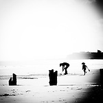 Silhouette of children playing on beach with Abbey in background