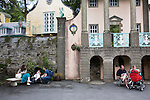 "Portmeirion, in North Wales, is a resort, where no one has ever lived. A self-taught Welsh architect named Sir Clough Williams-Ellis built it out of architectural salvage between the 1920s and 1970s, loosely based on his memories of trips to Portofino. Including a pagoda-shaped Chinoiserie gazebo, some Gothic obelisks, eucalyptus groves, a crenellated castle, a Mediterranean bell tower, a Jacobean town hall, and an Art Deco cylindrical watchtower. He kept improving Portmeirion until his death in 1978, age 94. It faces an estuary where at low tide one can walk across the sands and look out to sea. At high tide, the sea is lapping onto the shores. Every building in the village is either a shop, restaurant, hotel or self-catering accomodation. The village is booked out at high season, with numerous wedding receptions at the weekends. Very popular amongst the English and Welsh holidaymakers. Many who return to the same abode season after season. Hundreds of tourists visit every day, walking around the ornamental gardens, cobblestone paths, and shopping, eating ice-creams, or walking along the woodland and coastal paths, amongst a colourful assortment of hydrangea, rhododendrons, tree ferns and redwoods. The resort boasts two high class hotels, a la carte menus, a swimming pool, a lifesize concrete boat, topiary, pools and wishing wells. The creator describes the resort as ""a home for fallen buildings,"" and its ragged skyline and playful narrow passageways which were meant to provide ""more fun for more people."" It does just that.///Couples with young babies in pushchairs. Ornamental central gardens of Portmeirion village. Flanked by Dome Gallery, Gothic tower, Renaissance collonades, with lwans, flowerbeds, topiary, pools and fountains."
