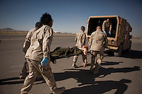 A US Army soldier wounded in an IED (improvised explosive device) blast is loaded into a waiting ambulance at Kandahar airfield.