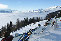 Switzerland. Valais. Crans Montana. Winter ski resort. A line of persons sit in the sun on plastic chairs and are enjoying a sunbath. The fog is covering the Rhone valley. © 2005 Didier Ruef