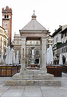 General view of capital, known as the Tribuna or Berlina, Piazza delle Erbe, Verona, Italy. Built before the 13th century, the Praetorians sat under it for the swearing in ceremony, when they took office. The Piazza delle Erbe (Square of Herbs) stands on the old Roman Forum, and remains the centre of city life. In the background are 14th century Gardello Tower and the Baroque Palazzo Maffei. Picture by Manuel Cohen.