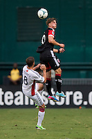 Chris Tierney (8) of the New England Revolution goes up for a header with Conor Doyle (30) of D.C. United during a Major League Soccer game at RFK Stadium in Washington, DC.  New England defeated D.C. United, 2-1.
