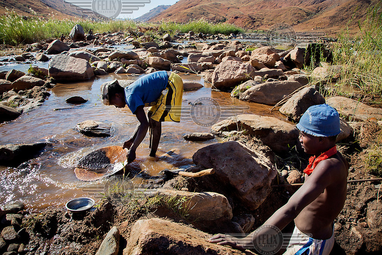 Two children pan for gold, filtering the sediment from the bottom of the Mahajilo River.
