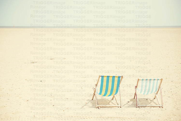 Deck chairs sitting empty on a long deserted beach