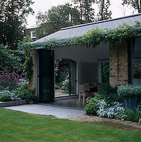 A contemporary rear extension to this listed Georgian property houses a dining room that opens onto the garden