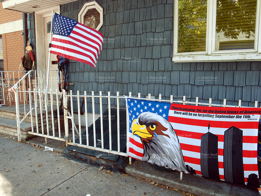 """USA. New York City. Brooklyn. Outside a private house on the railing, a banderole with a drawing of a bald eagle, an american flag and the Twin Towers ( World Trade Center ). The words say: """"Time is passing. Yet, for the United States of Amercia, there will be no forgetting. September the 11th 2001. Georges W. Bush"""".  American flag blowing in the wind. Near the door's entrance, an Halloween house decoration. 20.10.2011 © 2011 Didier Ruef"""
