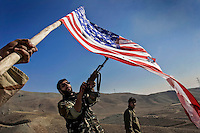 A soldier from the Iranian Revolutionary Guard (Basij) shoots up a US flag with his AK47.