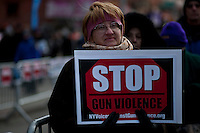 A woman holds a poster as she takes part during a rally against gun violence in Harlem March 21, 2013 in New York City . VIEWpress/ Kena Betancur.