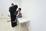 Rufiedah, who asked that her last name not be used for security reasons, comforts her son as he waits for the doctor at a clinic in Madaba, a sprawling Palestinian refugee camp in Jordan that has grown in recent years with the arrival of women like Rufiedah, who came to Madaba in 2014 from a village near Damascus, Syria. As a result, the more than 25,000 Palestinians in Madaba have been joined by more than 12,000 Syrians. The  Department of Service for Palestinian Refugees of the Middle East Council of Churches, a member of the ACT Alliance, provides a variety of services here, including medical care.