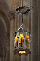 Reliquary in the form of an octagonal tower and a dove, by Goudji, French sculptor and goldsmith, b. 1941, commissioned by the Communaute des Premontres de Conques, installed and blessed 12th October 2014, suspended between the columns of the apse in the Abbatiale Sainte-Foy de Conques or Abbey-church of Saint-Foy, Conques, Aveyron, Midi-Pyrenees, France, a Romanesque abbey church begun 1050 under abbot Odolric to house the remains of St Foy, a 4th century female martyr. The reliquary is illuminated at night and invites prayer for persecuted Christians and hostages. The church is on the pilgrimage route to Santiago da Compostela, and is listed as a historic monument and a UNESCO World Heritage Site. Picture by Manuel Cohen. - Further clearance required, please contact us