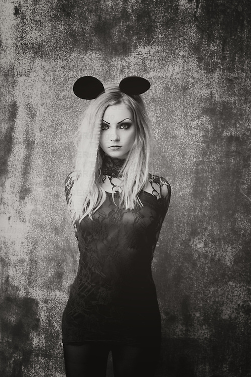 black-white photo of young woman with blonde hair wearing a black lace dress and wearing mouse ears wearing a heart ring