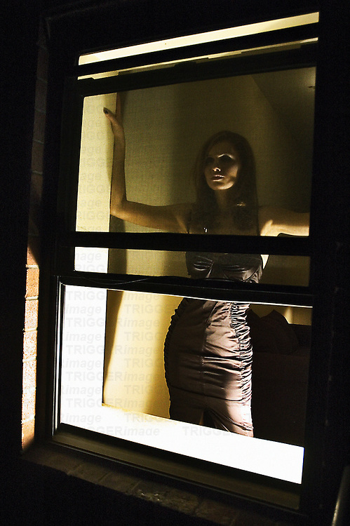 A young woman standing by an open window