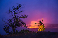 At dusk, a Hawaiian hula dancer in traditional attire dances in honor of the goddess Pele at Halema'uma'u Crater, Island of Hawai'i.