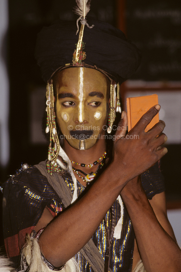 Hamdalaye, Niger, Africa - Fulani Wodaabe Dancer Checking Appearance in a Mirror prior to a Dance.