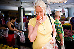 Kay Ferrier smells a fresh peach at the Sunday Certified Farmers' Market in Sacramento, California.