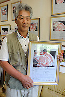 CEO Kazutaka Seto holds a Kobe beef certificate in his office, Maruse Stockbreeding Inc, Hyogo Prefecture, Japan, June 25, 2009.