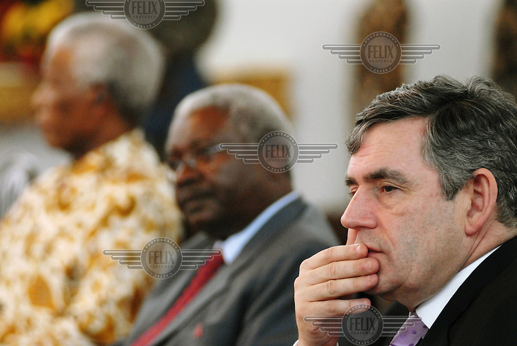 British Chancellor of the Exchequer Gordon Brown (R) sits alongside president Armando Guebuza (C) and former South African president Nelson Mandela (L) at the presidential palace in Maputo during talks about education in the developing world.