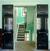 Double doors open from the living room onto a landing with a stripped parquet floor