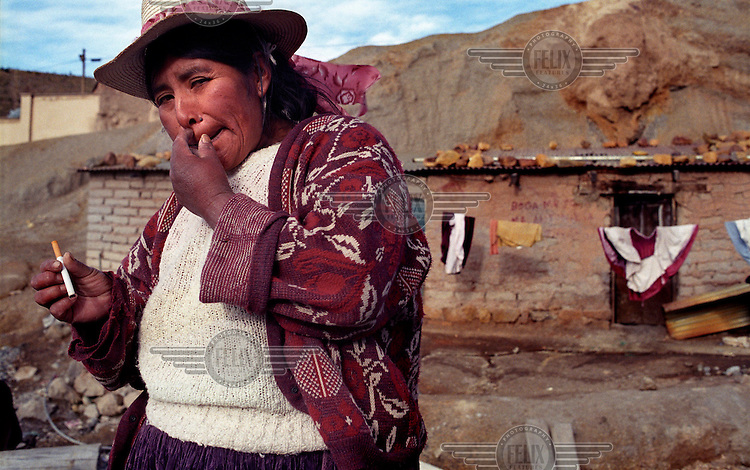 37 year old Angelica Solis holds a cigarette in front of her house on the Cerro Rico (rich mountain). Silver ore deposits on this mountain provide jobs for over 20,000 miners in the town of Potosi. The number of mines in the area is estimated at 500..