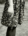 A young woman in a print dress holding an old-fashioned revolver<br /> [This photograph is currently licensed through Millennium Images - please contact the photographer for details]