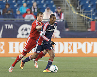 New England Revolution forward Jerry Bengtson (27) dribbles as Toronto FC defender Steven Caldwell (13) pressures. In a Major League Soccer (MLS) match, the New England Revolution (blue) defeated Toronto FC (red), 2-0, at Gillette Stadium on May 25, 2013.